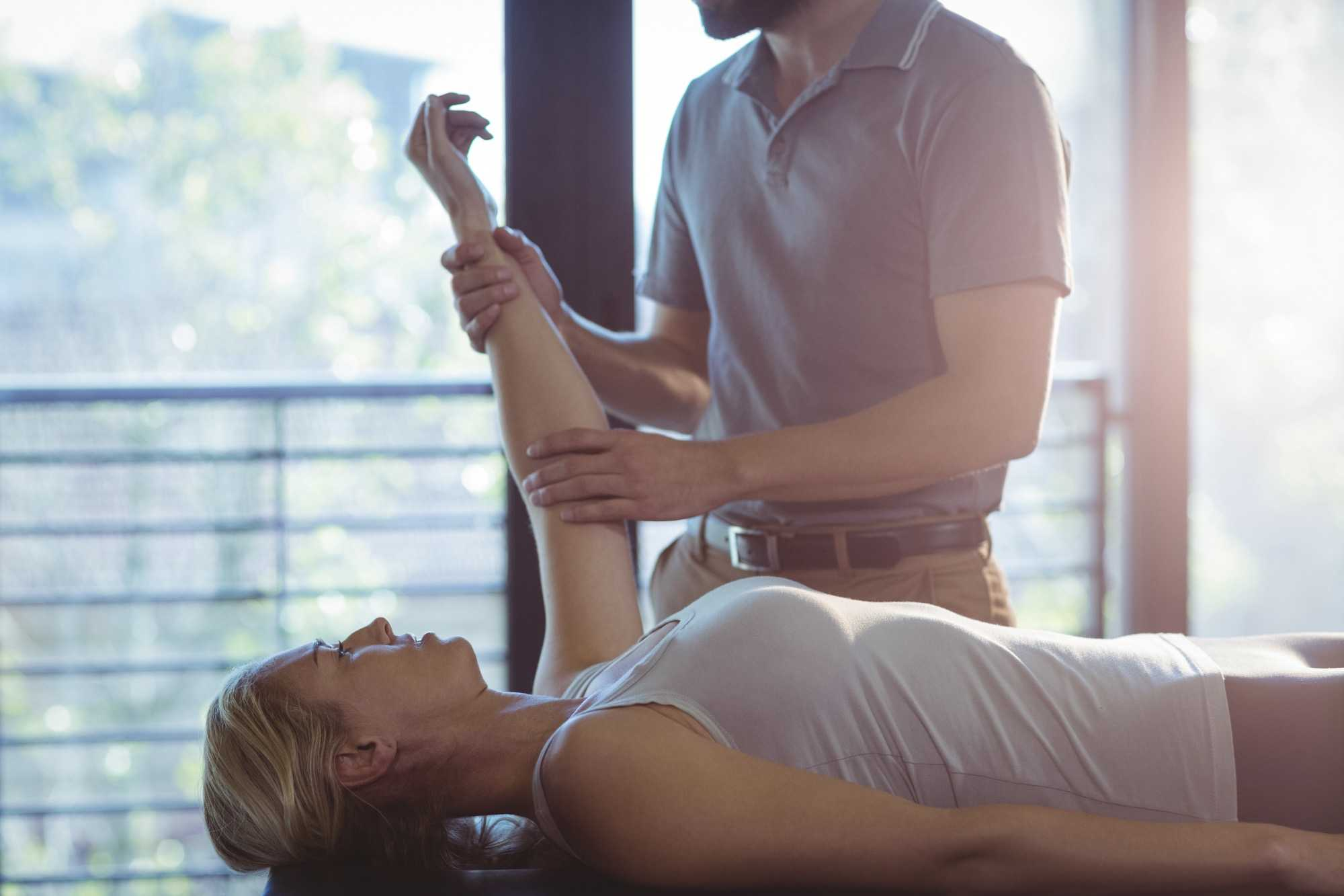 2woman-receiving-hand-therapy-exercises-from-physio-5N3LK8G